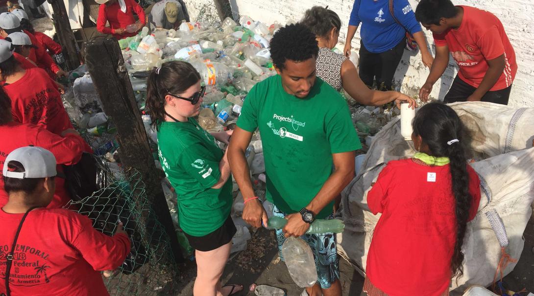En su voluntariado en verano para jóvenes, voluntarios participan en limpiezas de playa.